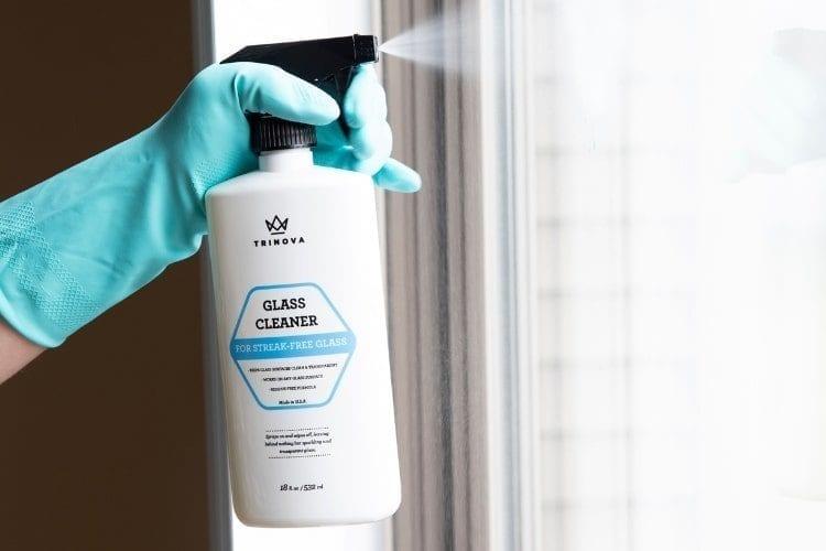 Spraying TriNova Glass Cleaner on patio door