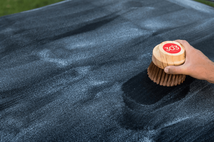 After applying 303 Convertible Top Cleaner, lightly rub it in with a brush, like the 303 Convertible Top Brush.