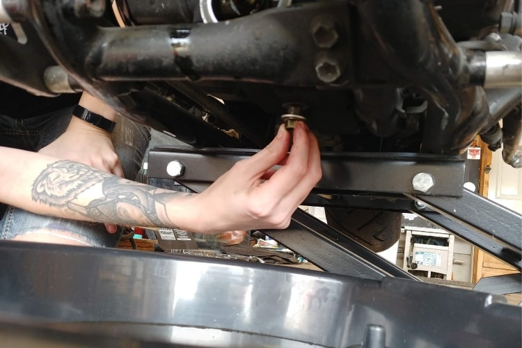 Insert oil pan drain bolt by hand.
